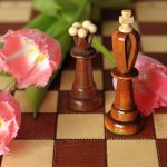 Pink flowers on a chess board next to chess pieces