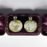 Two round perfume bottles sit nestled in a brown leather box lined with purple satin. The perfume bottles are pale yellow citron with white cameo flowers and a butterfly.