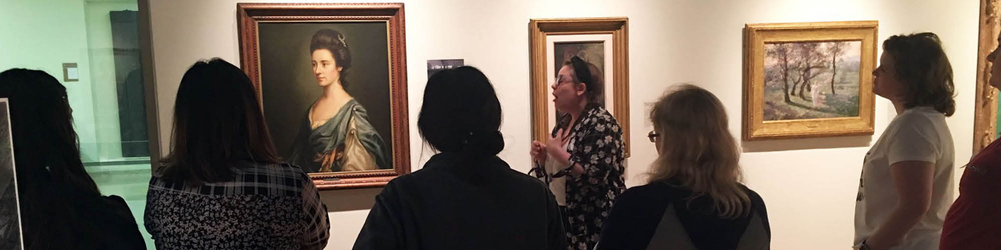 Female gallery staff member talks to a group of women in the gallery as they all look at a portrait of a Victorian era woman on the wall.