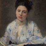 Portrait of a woman with dark hair on top of her head and white blouse with light blue flowers.