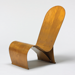 Curvy wooden chair in a honey-colored finish; sits low to the ground; one curved piece