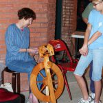 Person sits at spinning wheel and demonstrates techniques as people look on.
