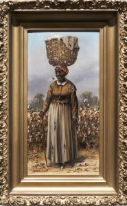 Female African American figure in a worn dress and a red kerchief standing in a cotton field, balancing a large basket of cotton on her head. She is smoking a corncob pipe and holds a walking stick in her proper right hand.