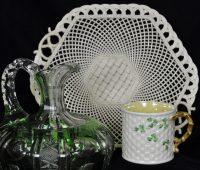 In the background is a white, woven porcelain cake plate; in the foreground left is a green and clear cut glass decanter; in the foreground right is a white porecelain cup with a weave pattern and green shamrock leaves