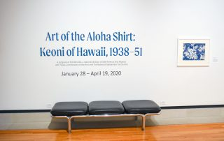 """Title wall of the exhibition in the Stark Galleries; Wall reads """"Art of the Aloha Shirt: Keoni of Hawaii, 1938-51; black bench below the title wall; framed painting of a blue and white Hibiscus Hawaiian shirt print"""