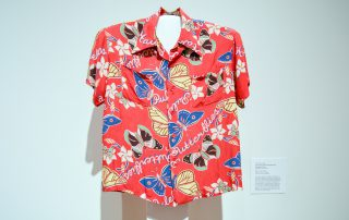 """Aloha shirt featuring blue, yellow, and green/black butterflies on a red background. The word """"butterflies"""" is written several times across the shirt in a cursive, white font"""
