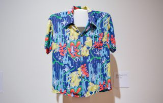 Aloha shirt featuring green, red, and yello seaweed and sea creatures on a bright blue background