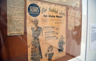 Framed newspaper clippings of an old advertisement for Sears featuring illustrations of women and girls in Aloha themed dresses and tops