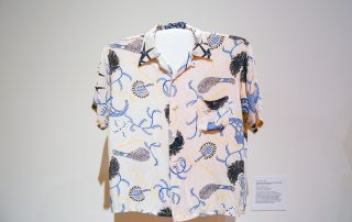 Aloha shirt with abstract blue and yellow designs on a white background