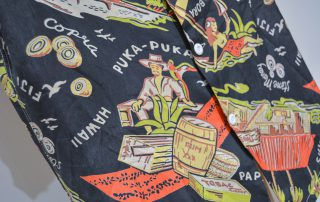 """Aloha shirt with black background showing a woman and a boat anchor, barrels of goods, a man in a straw hat, a hut with a sign that says """"Trader Joe's"""", and a ship"""